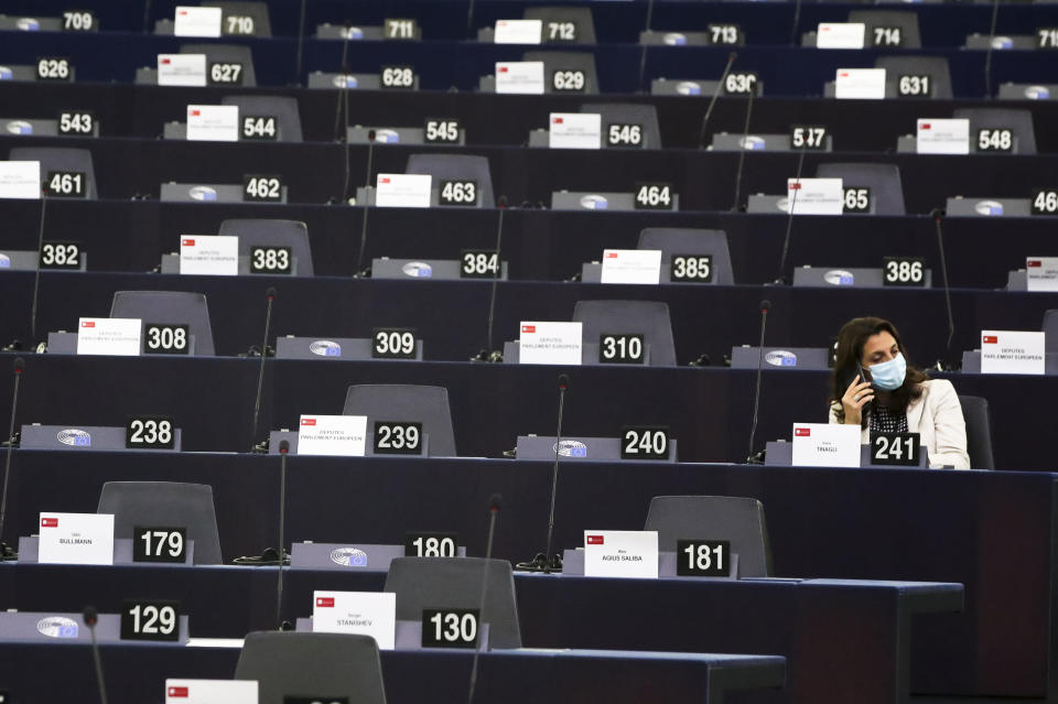 An MEP waits in the plenary for the session to begin at the European Parliament in Strasbourg, France, Wednesday, Sept. 15, 2021. The European Union announced Wednesday it is committing 200 million more coronavirus vaccine doses to Africa to help curb the COVID-19 pandemic on a global scale. (Yves Herman, Pool via AP)