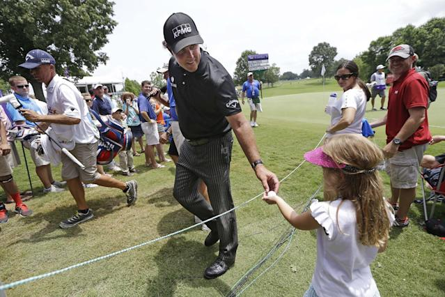 Phil Mickelson gives a golf ball to Taylor Hardin, 6, as he leaves the 17th green during the second round of the St. Jude Classic golf tournament Saturday, June 7, 2014, in Memphis, Tenn. Mickelson shot a par on the hole. Bad weather on Friday caused the second round to continue into Saturday. (AP Photo/Mark Humphrey)