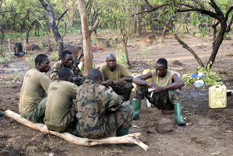 In this photo taken Thursday, April 19, 2012, Ugandan soldiers hunting for fugitive warlord Joseph Kony eat breakfast before embarking on a 14-kilometer patrol near the River Vovodo, in the Central African Republic. The hunt for notorious rebel leader Joseph Kony is heating up on international radars, but Ugandan foot soldiers who have spent years searching for the man are starting to ask a question their top commanders prefer to ignore: Is it possible he is dead? (AP Photo/Rodney Muhumuza)