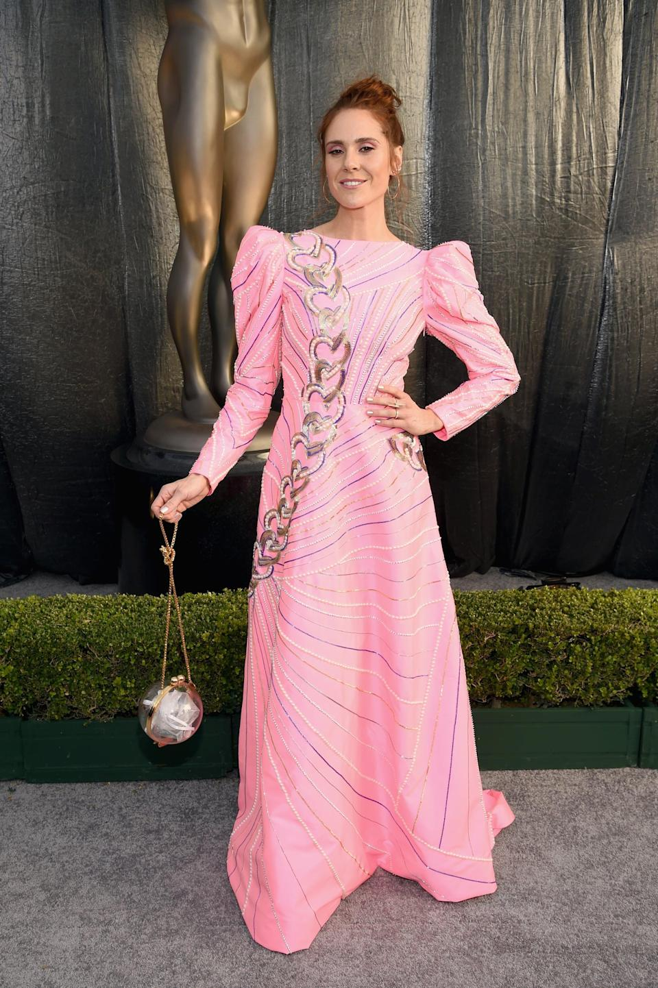 <p>Wearing a pink Manish Arora gown with a sparkly clutch.</p>