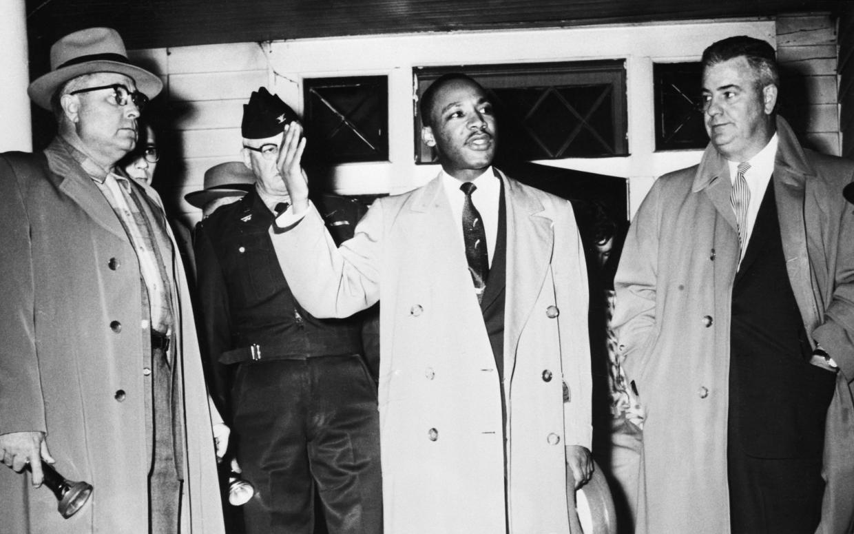 Martin Luther King Jr. urges calm from the porch of his home, which was damaged by a bomb during a boycott of the Montgomery, Ala.., bus system to protect segregation in 1956.  With him, left to right, are: Fire Chief R.L. Lampley; Mayor W.A. Gayle (in uniform) and City Police Commissioner Clyde Sellers. (Photo: Bettmann/Getty Images)