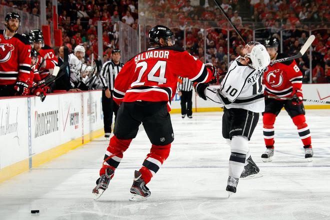 NEWARK, NJ - JUNE 09: Mike Richards #10 of the Los Angeles Kings draws contact from Bryce Salvador #24 of the New Jersey Devils during Game Five of the 2012 NHL Stanley Cup Final at the Prudential Center on June 9, 2012 in Newark, New Jersey.  (Photo by Bruce Bennett/Getty Images)