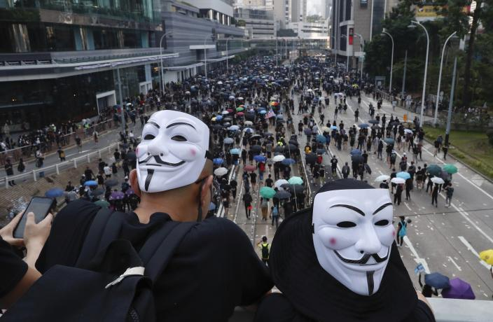 Anti-government protesters wearing masks march past police headquarters in Hong Kong, Oct. 1, 2019. (Photo: Gemunu Amarasinghe/AP)