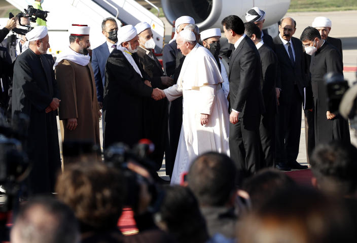 Muslim clerics welcome Pope Francis as he arrives in Irbil, Iraq, Sunday, March 7, 2021. Pope Francis arrived in northern Iraq on Sunday, where he planned to pray in the ruins of churches damaged or destroyed by Islamic State extremists and celebrate an open-air Mass on the last day of the first-ever papal visit to the country. (AP Photo/Hadi Mizban)