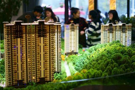 People look at miniature models of new apartments at a property sale centre in Yichang, Hubei province, November 21, 2015. REUTERS/Stringer/Files