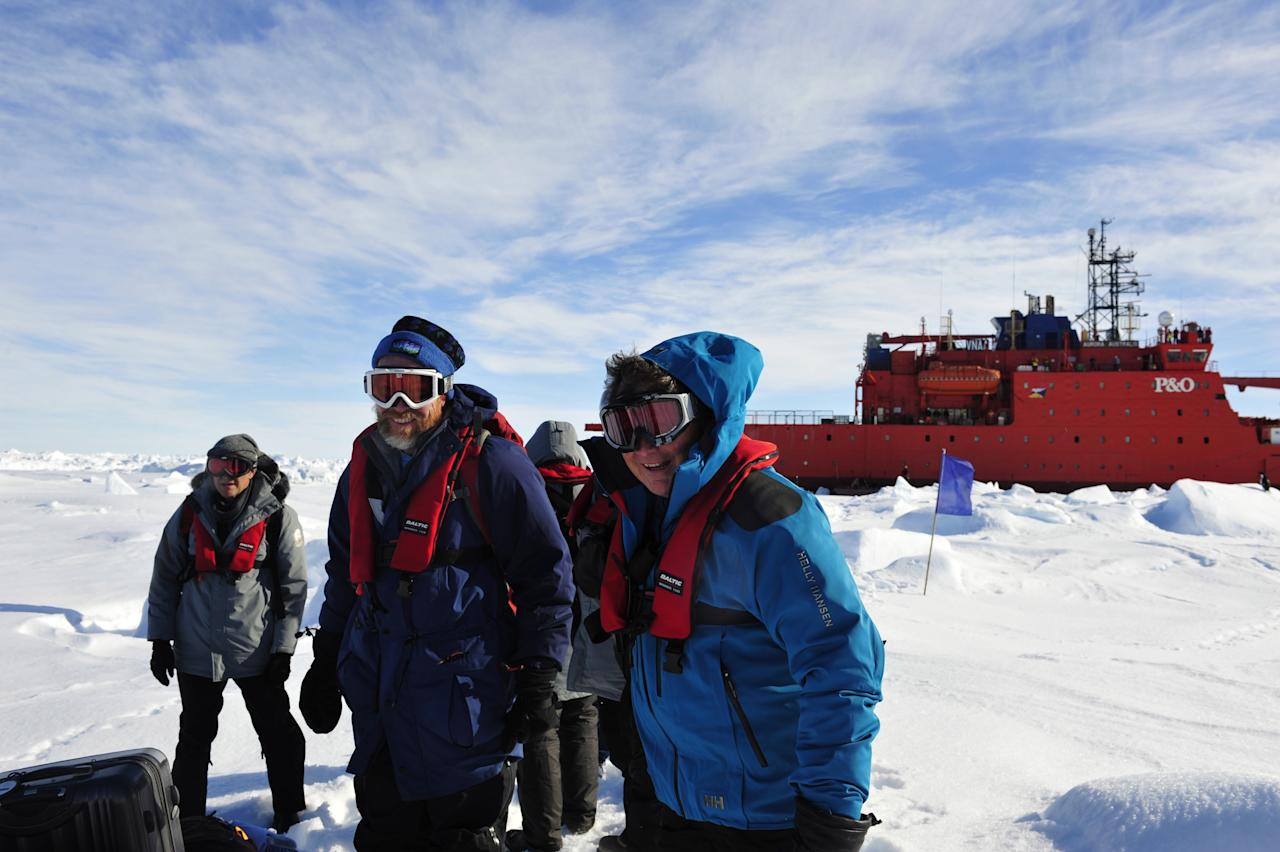 In this photo provided China's official Xinhnua News Agency, the first group of passengers who were aboard the trapped Russian ship MV Akademik Shokalskiy arrive at a safe surface off the Antarctic Thursday, Jan. 2, 2014. A helicopter rescued all 52 passengers from the research ship that has been trapped in Antarctic ice, 1,500 nautical miles south of Hobart, Australia, since Christmas Eve after weather conditions finally cleared enough for the operation Thursday. (AP Photo/Xinhua, Zhang Jiansong) NO SALES