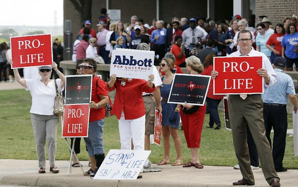 People hold signs protesting against State Sen. Wendy Davis as her supporters line up in the background outside the venue hosting a rally Thursday, Oct. 3, 2013, in Haltom City, Texas. Davis was expected to formally announce her campaign for governor Thursday, becoming the first Democrat to make an official bid for a statewide office. (AP Photo/LM Otero)