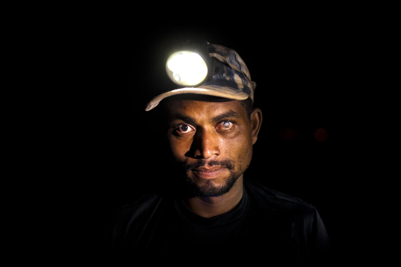 In this May 29, 2012 photo, Wallace de Souza, 34, poses for a portrait at the Jardim Gramacho, one of the world's largest open-air landfills, in Rio de Janeiro, Brazil. Jardim Gramacho, a vast, seaside mountain of trash where thousands of people made a living sorting through the debris by hand, is closing after three decades in service. Souza lost his sight in his left eye when acid splashed his eye while searching for recyclable materials at the dump. (AP Photo/Victor R. Caivano)