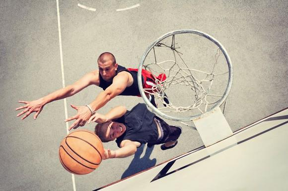Two players battle over a basketball under the hoop.