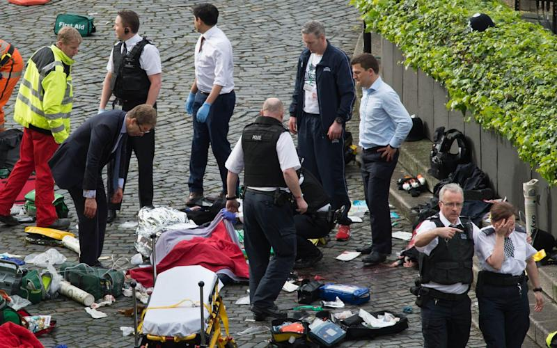 Conservative MP Tobias Ellwood (left) stands amongst the emergency services at the scene outside the Palace of Westminster - Credit: Stefan Rousseau/PA