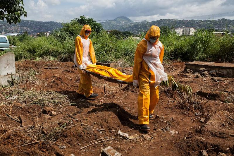 A team of funeral agents educated on the burial of Ebola victims carries a body to put it in a grave in Freetown, Sierra Leone, on October 10, 2014 (AFP Photo/Florian Plaucheur)