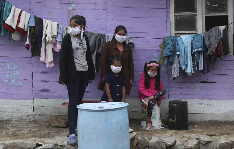 Wearing masks to prevent the spread of the new coronavirus, the Sanchez sisters Silvana, left, Maria, second left back, Luisa, second right front, and Brittany stand in from of their home in Puente Piedra shantytown on the outskirts of Lima, Peru, Monday, June 1, 2020. (AP Photo/Martin Mejia)