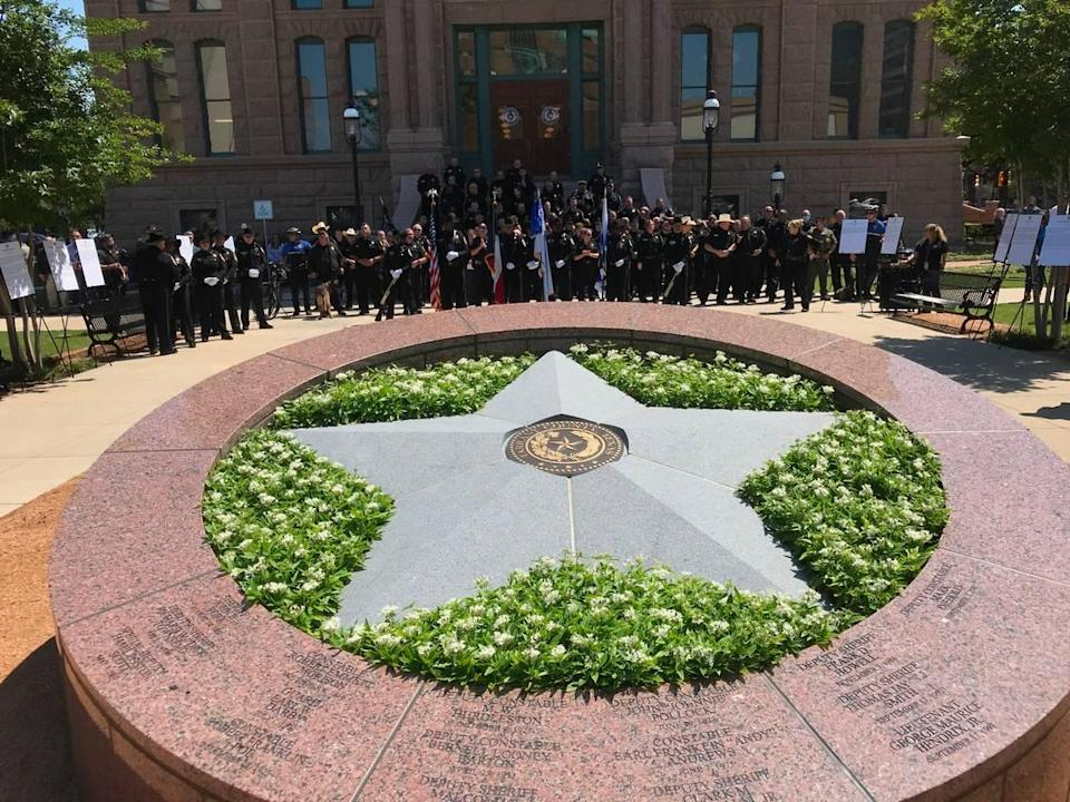 Dozens of Tarrant County, TX law enforcement officials face the newly unveiled Law Enforcement Memorial outside of the 1895 Courthouse. The names of 16 fallen officers grace the memorial.