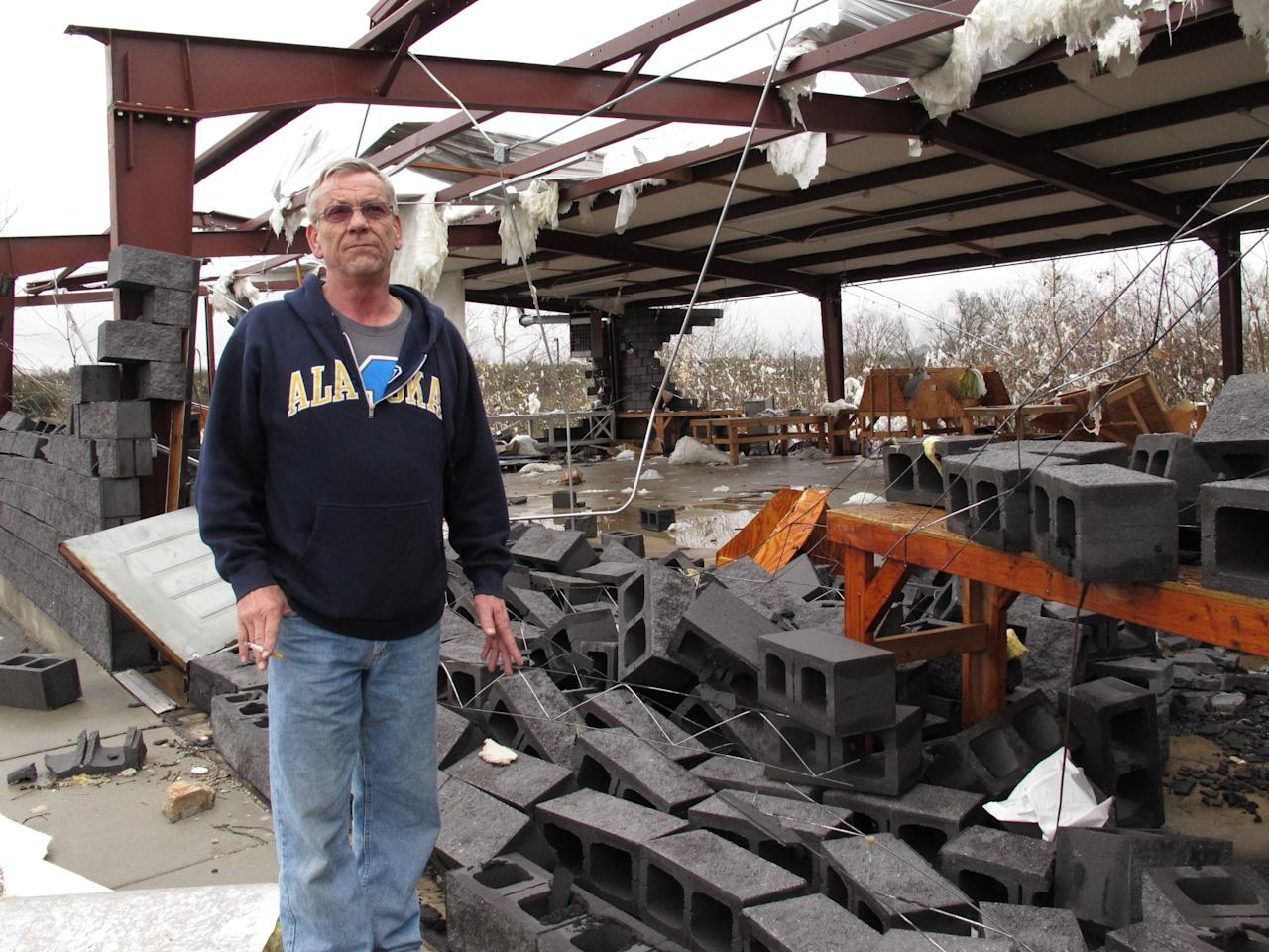 Rick Martin stands in front of a Tennessean newspaper distribution center in Mount Juliet, Tenn., on Wednesday, Jan. 30, 2013, that was destroyed in a severe storm. Forecasters examined the damage path of 4.6 miles Wednesday morning and estimated the peak wind speed at 115 mph, qualifying the tornado as an EF-2 twister. The path of damage was about 150 yards wide. (AP Photo/Kristin M. Hall)