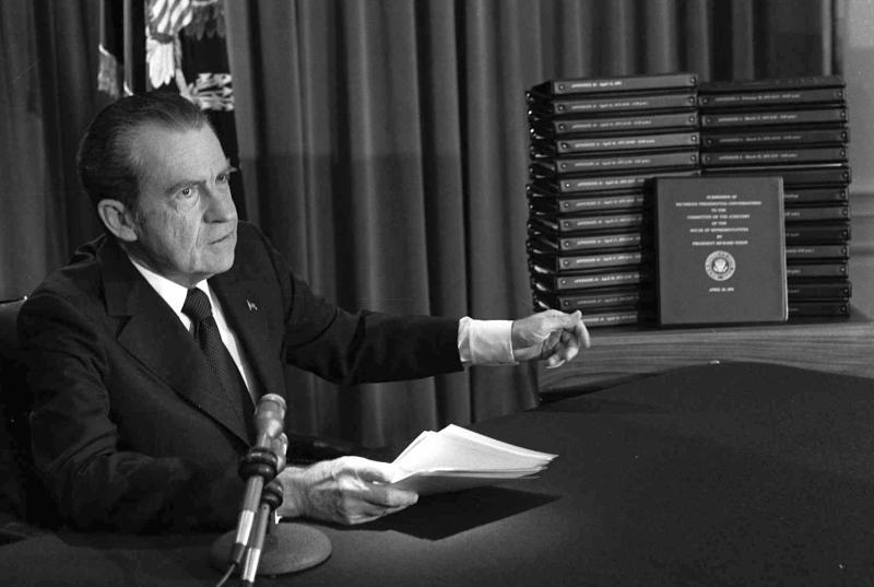 FILE - In this April 29, 1974, file photo, President Richard M. Nixon points to the transcripts of the White House tapes after he announced during a nationally-televised speech that he would turn over the transcripts to House impeachment investigators, in Washington.  Donald Trump joins a small group of fellow presidents now that he's the subject of an official impeachment inquiry in the House of Representatives. Only three of his predecessors underwent similar proceedings: Andrew Johnson and Bill Clinton, who were acquitted after trials in the Senate, and Richard Nixon, who resigned to avoid being impeached in connection with the Watergate scandal.  (AP Photo/File)