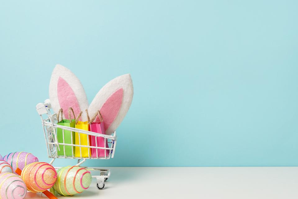 Colorful painted Easter egg with shopping cart, bunny ears and paper bags , blue background, copy space