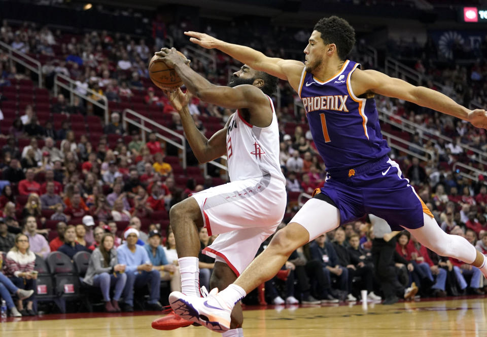 Houston Rockets' James Harden (13) goes up for a shot as Phoenix Suns' Devin Booker (1) reaches to foul him during the first half of an NBA basketball game Saturday, Dec. 7, 2019, in Houston. (AP Photo/David J. Phillip)