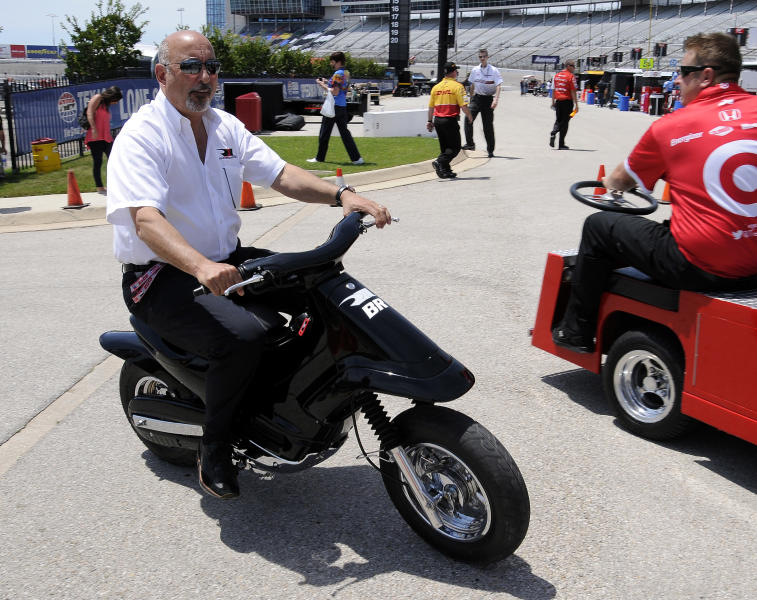 Bobby Rahal, part owner of Rahal Letterman Lanigan Racing heads onto pit road while riding a scooter before the start of a practice session for Saturday's Firestone 550 auto race at Texas Motor Speedway Friday, June 7, 2013, in Fort Worth, Texas. (AP Photo/Larry Papke)