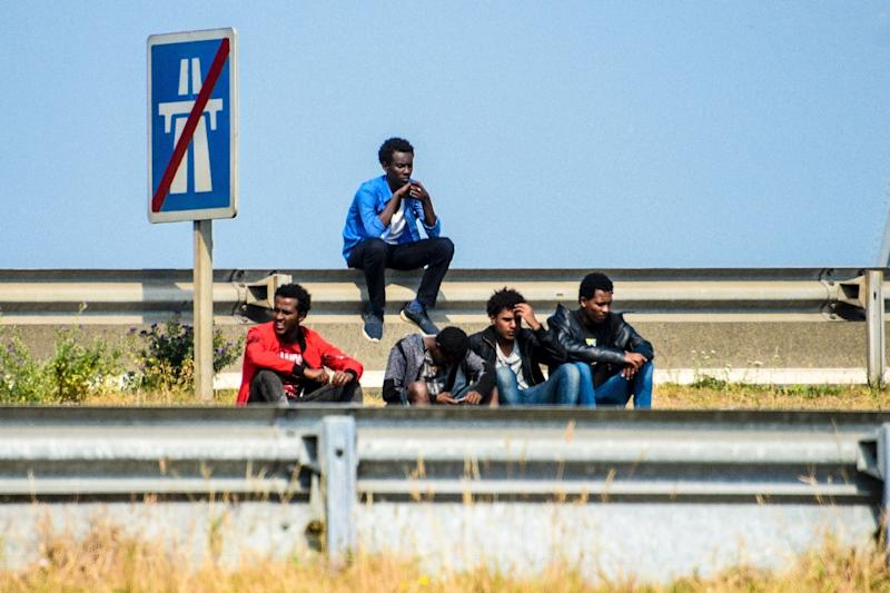 Migrants wait along the ring road leading to the port of Calais, northern France, in June 2017 (AFP Photo/DENIS CHARLET)