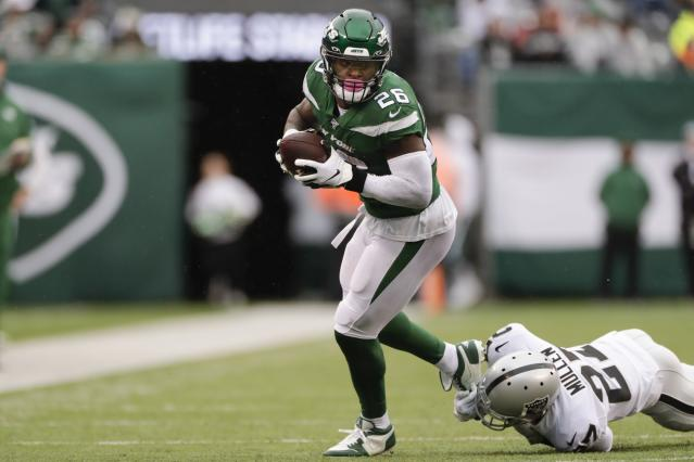 New York Jets running back Le'Veon Bell (26) breaks a tackle by Oakland Raiders' Trayvon Mullen (27) during the first half of an NFL football game Sunday, Nov. 24, 2019, in East Rutherford, N.J. The Jets won 34-3. (AP Photo/Adam Hunger)