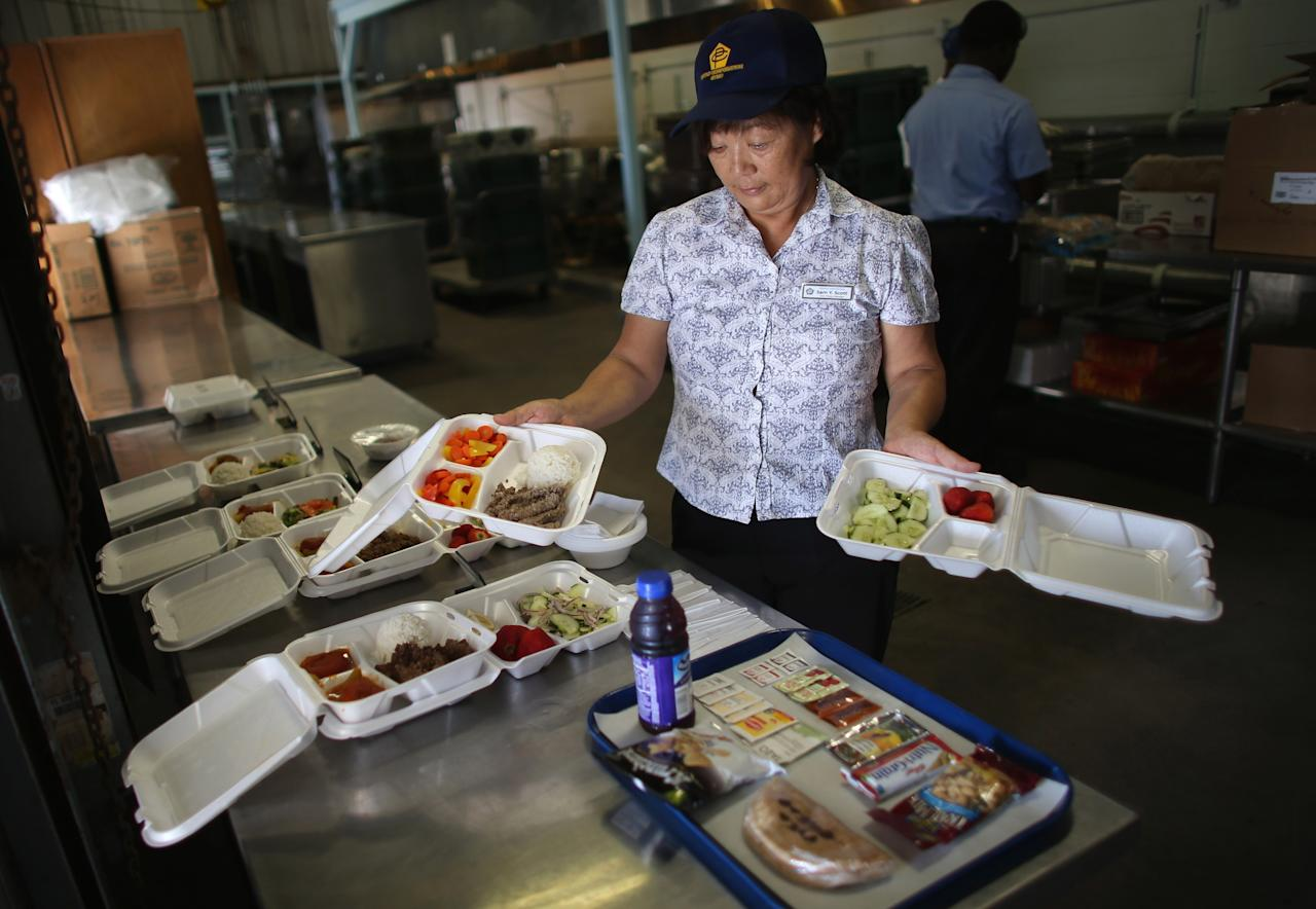 GUANTANAMO BAY, CUBA - JUNE 26: (EDITORS NOTE: Image has been reviewed by the U.S. Military prior to transmission.) Sam Scott shows off food that has been prepared in a kitchen for the detainees at the U.S. military prison for 'enemy combatants' on June 26, 2013 in Guantanamo Bay, Cuba. President Barack Obama has recently spoken again about closing the prison which has been used to hold prisoners from the invasion of Afghanistan and the war on terror since early 2002. (Photo by Joe Raedle/Getty Images)