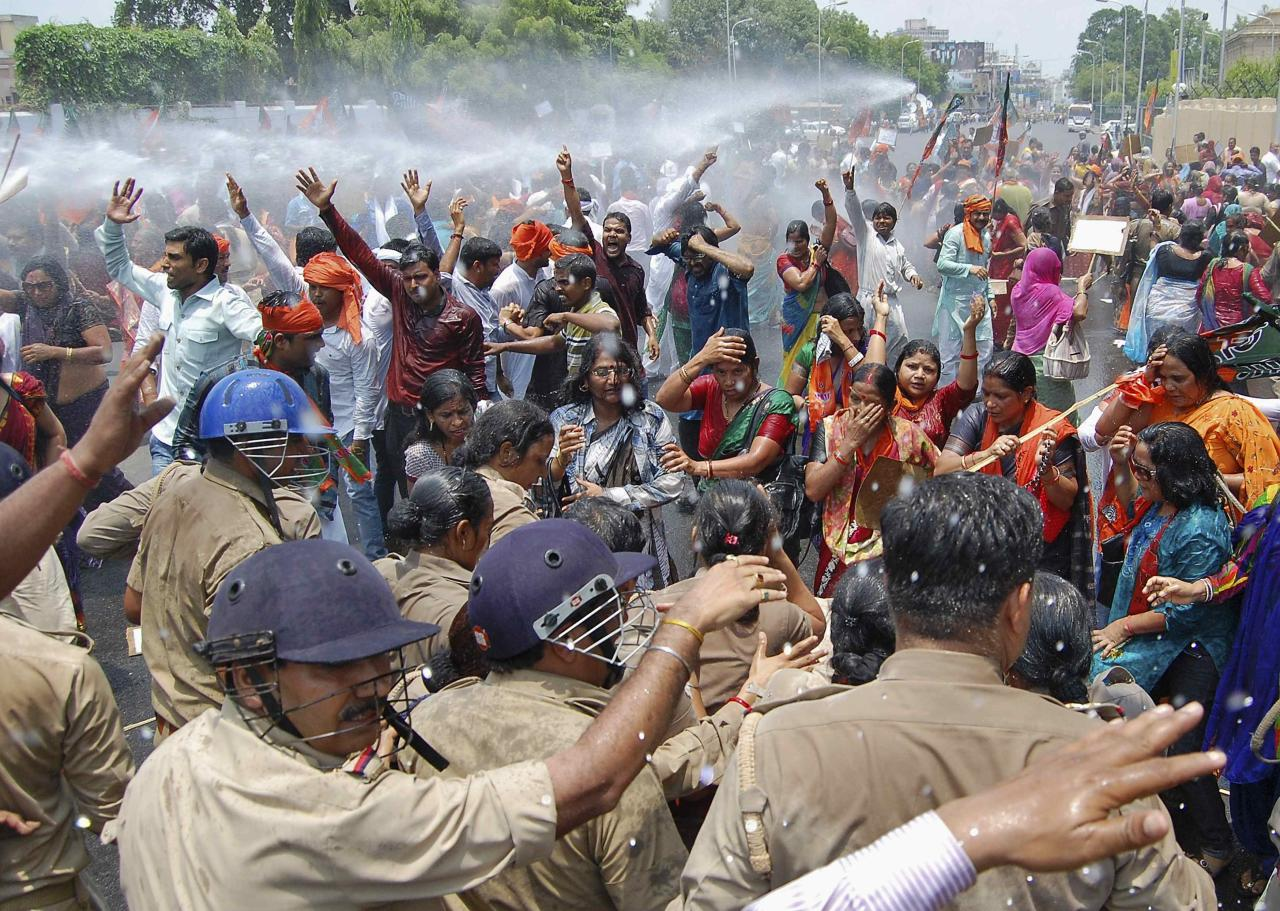 Supporters of Bharatiya Janata Party (BJP) shout slogans as police use a water cannon to stop them from moving towards the office of Akhilesh Yadav, the chief minister of the northern Indian state of Uttar Pradesh, during a protest against recent rape and hanging of two girls, in Lucknow June 2, 2014. Three men were arrested for the crime in Uttar Pradesh that underscored the enduring culture of sexual assault in India and the capacity for appalling violence between Hindu castes. Two policemen were held on suspicion of attempting to cover up the killings. On Monday, Modi's BJP sought to make political capital. Workers from the party accused the Uttar Pradesh state government, headed by Samajwadi Party, of negligence over the crimes and of being unfit to govern. Police fired water cannon at the protesters, who were demanding the state government be dismissed and the imposition of direct, presidential rule. REUTERS/Pawan Kumar (INDIA - Tags: POLITICS CRIME LAW CIVIL UNREST TPX IMAGES OF THE DAY)