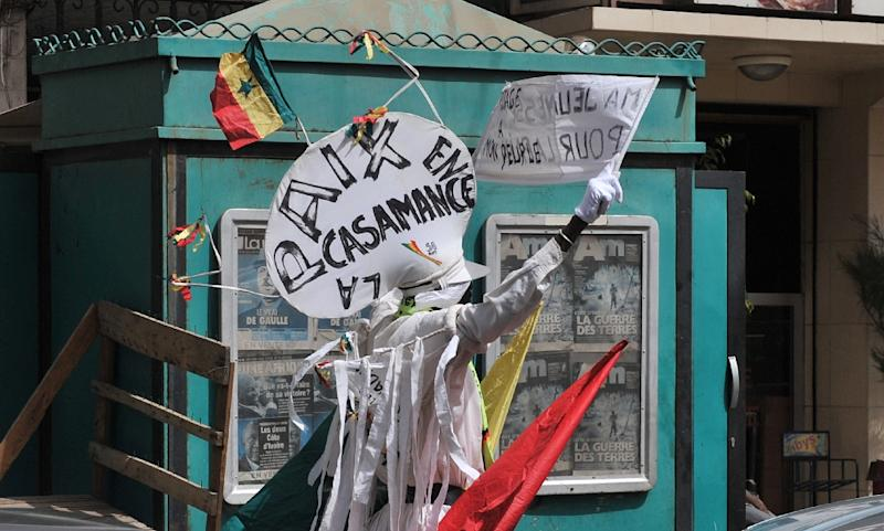 A demonstrator stands with placards asking for peace in Casamance on a street of Dakar  in 2012