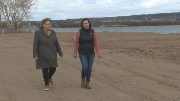 Jean Young, left, and her daughter Sara Young walk along the recently cleared RV lots near Deer Lake Beach. They are worried the company developing this land is not taking the environment into consideration. (Colleen Connors/CBC - image credit)