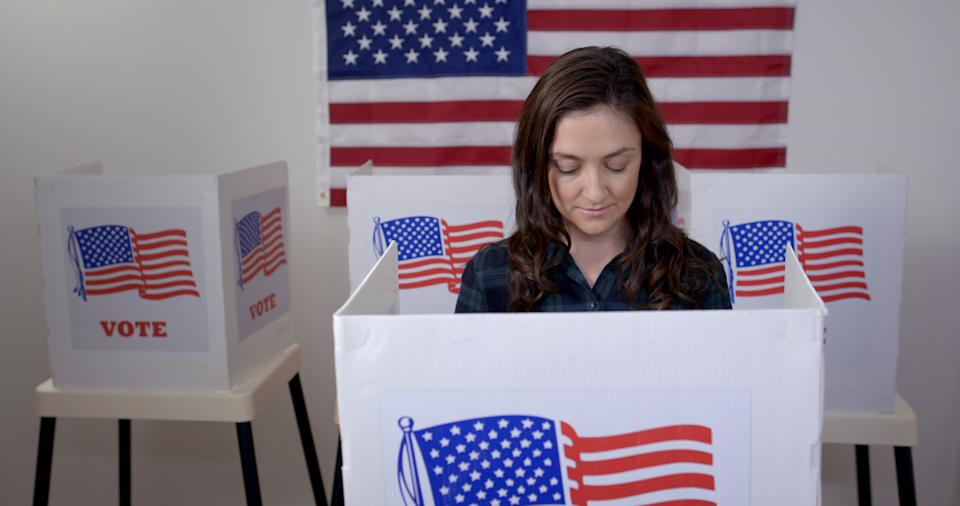 MS front view Caucasian American woman in plaid shirt in voting booth, casting vote at polling station. US flag on wall in background