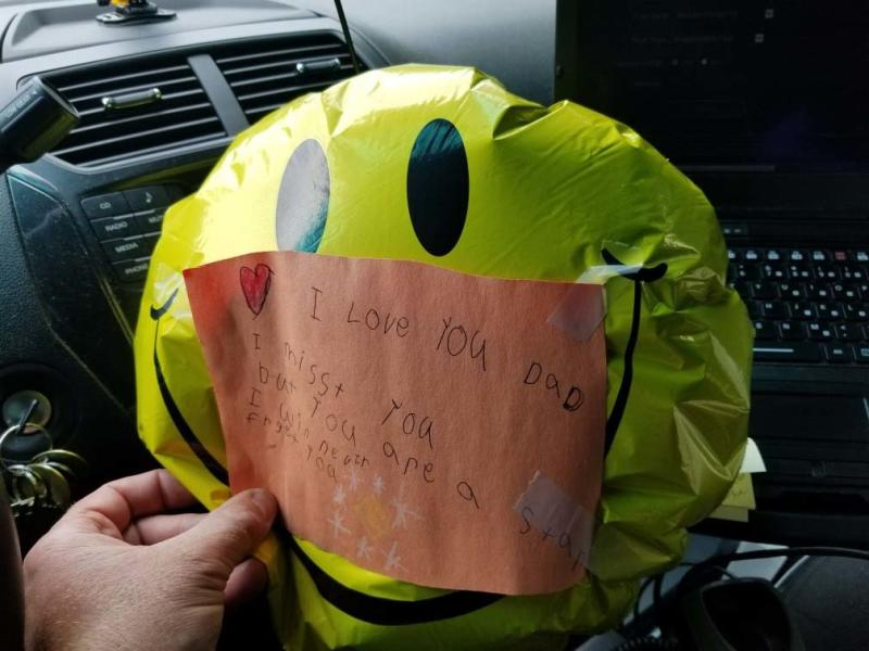 Yellow smiley face balloon with child's note to dead dad attached that was found by US police officer.