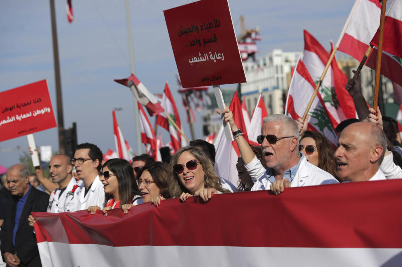 Anti-government doctors shout slogans during separate civil parade at the Martyr square, in downtown Beirut, Lebanon, Friday, Nov. 22, 2019.  Protesters gathered for alternative independence celebrations, converging by early afternoon on Martyrs' Square in central Beirut, which used to be the traditional location of the official parade. Protesters have occupied the area, closing it off to traffic since mid-October.  (AP Photo/Hassan Ammar)