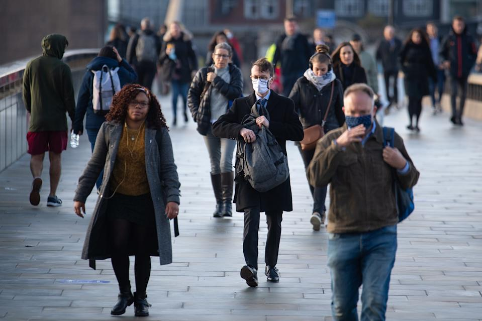 Commuters cross London Bridge, in central London, during morning rush hour after Prime Minister Boris Johnson set out a new three-tier system of alert levels for England following rising coronavirus cases and hospital admissions.