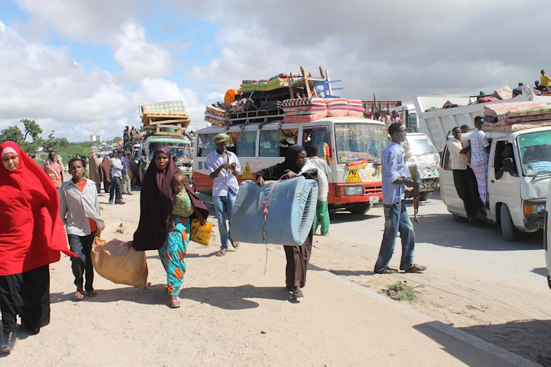 Somali civilians fleeing fighting in the Afgoye corridor carry their belongings as they pass across a checkpoint in Mogadishu, Somalia,Thursday, May 24, 2012.  Thousands of people in speeding trucks or pulling carts piled high with clothes and furniture fled a region north of Mogadishu on Thursday, as the sound of gunfire and explosions rocked the region. The Afgoye corridor has been a temporary shelter for hundreds of thousands of people seeking relief from fighting in the capital after Ethiopian troops entered Somalia in 2007 to fight al-Shabab militants. This week African Union and Somali troops moved into the Afgoye corridor for the first time in years to pursue al-Shabab. (AP Photo/Farah Abdi Warsameh)