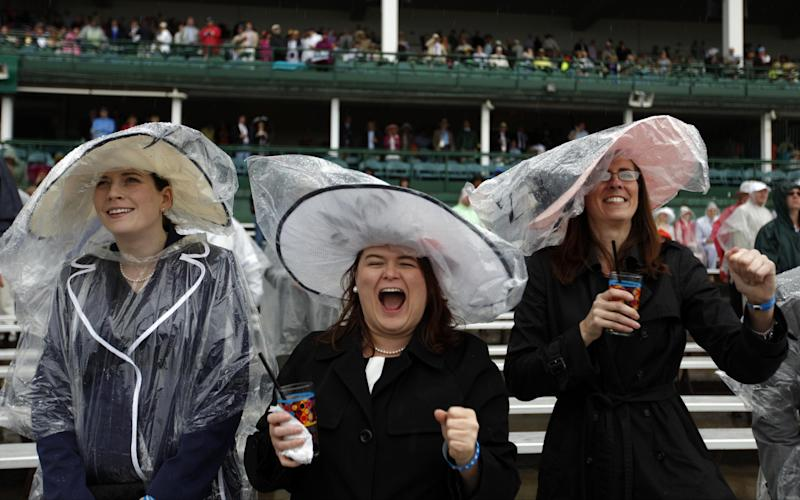 From left, Amanda Dugan, Bernadette Osborne and Tracy Clay watch the fourth race before the 139th Kentucky Derby at Churchill Downs Saturday, May 4, 2013, in Louisville, Ky. (AP Photo/David Goldman)