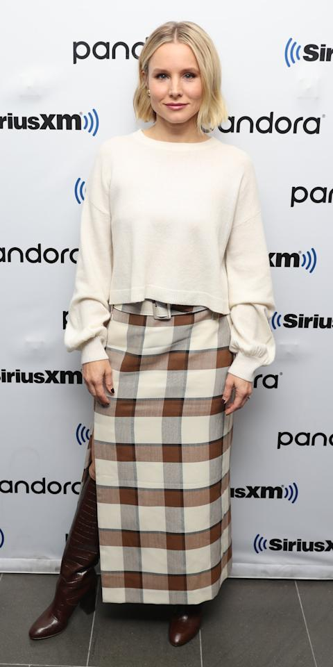 <p>During a visit to the Sirius XM studios, Kristen Bell wore an Alice + Olivia sweater, Staud skirt, Loeffler Randall boots, and Sarah Hendler earrings.</p>
