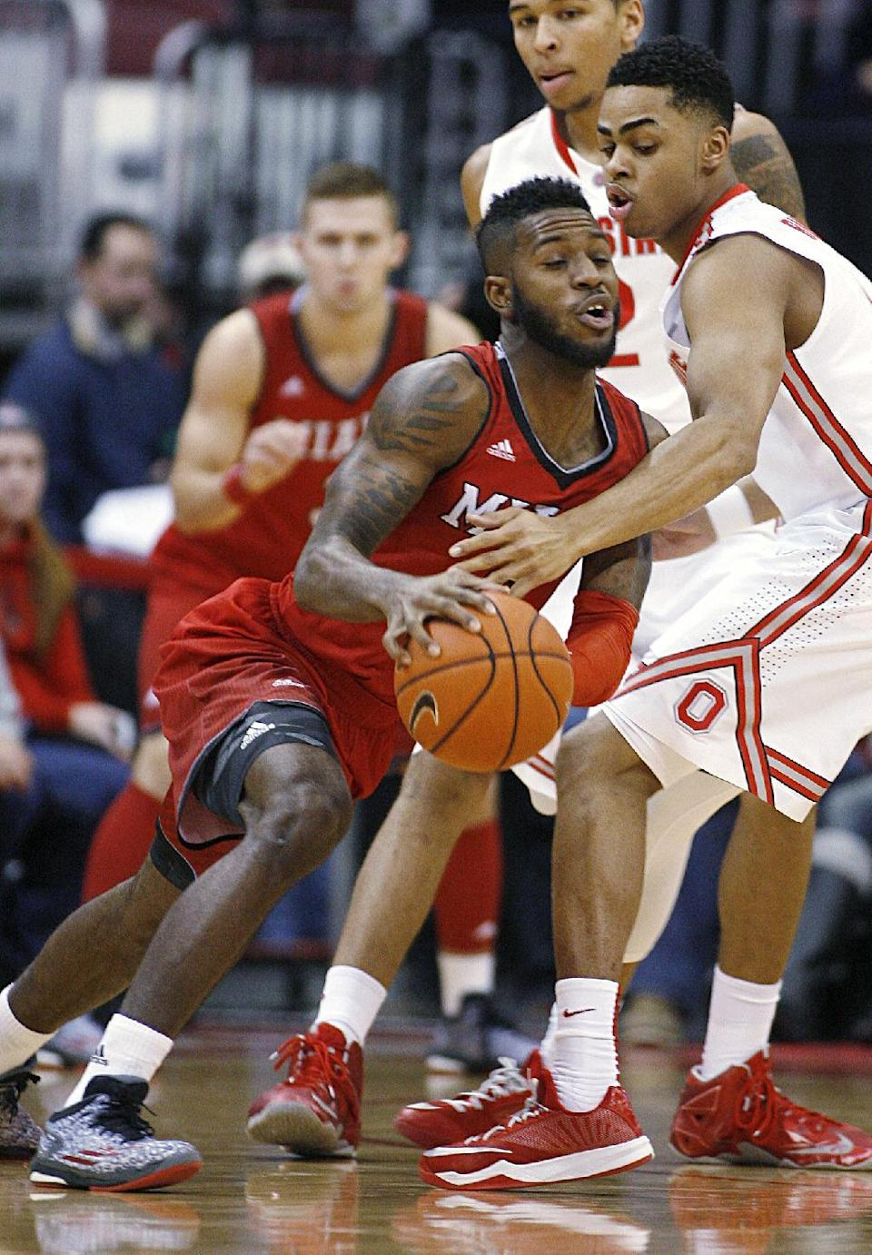 Ohio State's D'Angelo Russell (0), right, slows down Miami's Geovonie McKnight (0) in the first half of an NCAA basketball game, Monday, Dec. 22, 2014, in Columbus, Ohio. (AP Photo/Mike Munden)