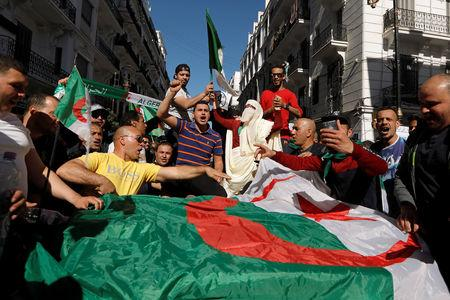 People carry their national flags as they protest over President Abdelaziz Bouteflika's decision to postpone elections and extend his fourth term in office, in Algiers, Algeria March 15, 2019. REUTERS/Zohra Bensemra
