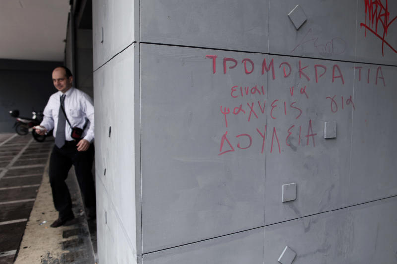 A man leaves an office of Labor Force Employment Organization (OAED) with a graffiti reading in Greek ''Terrorism = Job Seeking'' in central Athens, on Thursday, March 7, 2013. Unemployment in Greece dipped marginally to 26.4 percent in December, but experts warn that more significant improvements are unlikely in coming months. (AP Photo/Petros Giannakouris)