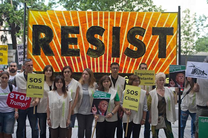 <p>Greenpeace protesters stand in silence with banners outside the U.S. embassy in Madrid, Spain, Friday, June 2, 2017. The protesters gathered at the gates of the United States embassy in the Spanish capital to protest President Donald Trump's decision to pull the world's second-largest carbon dioxide emitter out of the Paris climate agreement. Small banners read 'Climate SOS' and 'We'll go ahead without you' (AP Photo/Paul White) </p>