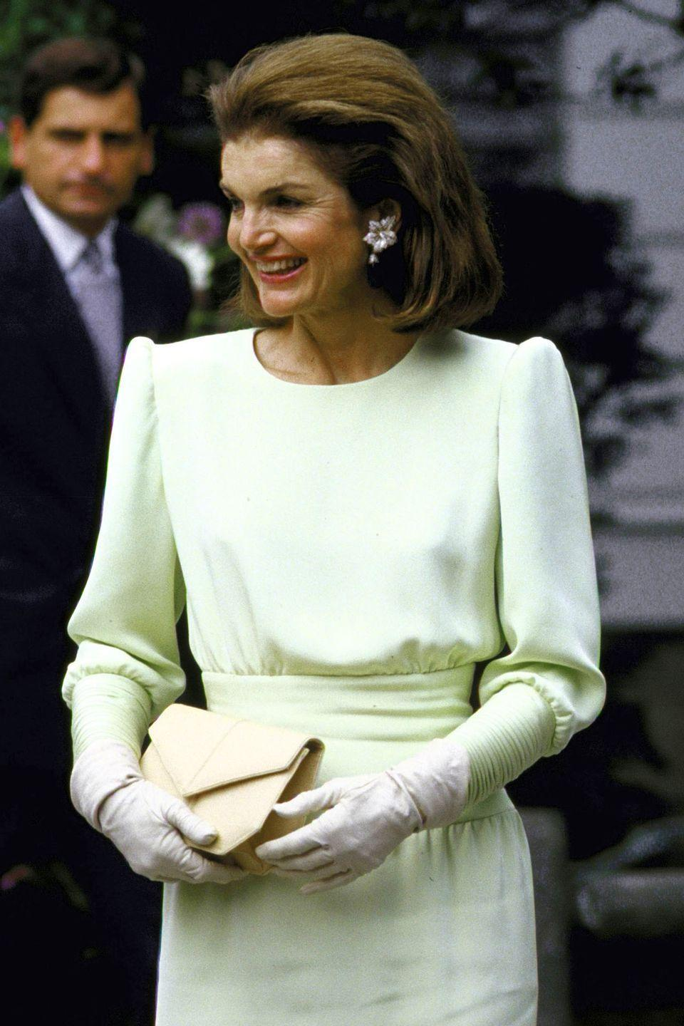<p>Even in the sometimes stylistically fraught mid-1980s, Kennedy-Onassis keeps her composure in a bit of a bold shoulder without going too over-the-top. Statement earrings and gloves finish the look. </p>