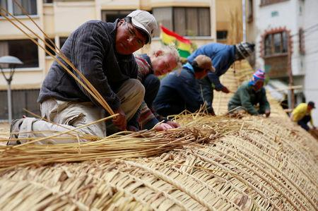 Builders work on top of the 'Viracocha III', a boat made only from the totora reed, as it is being prepared to cross the Pacific from Chile to Australia on an expected six-month journey, in La Paz, Bolivia, October 19, 2016. REUTERS/David Mercado