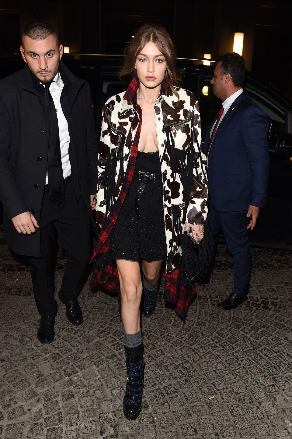 <p>In a cattle print fringed jacket, plaid flannel, black belted minidress, grey socks and heeled combat boots while attending the DSquared2 Volt Party in Milan.</p>