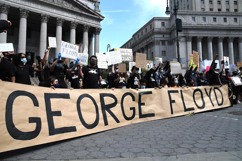 "NEW YORK, NEW YORK - MAY 29: Protestors gather behind a banner spelling the name of George Floyd, a black man who died after a white policeman kneeled on his neck during a ""Black Lives Matter"" protest on May 29, 2020 at Foley Square in New York City. Demonstrations are being held across the US after George Floyd died in police custody on May 25. (Photo by Kevin Mazur/Getty Images)"