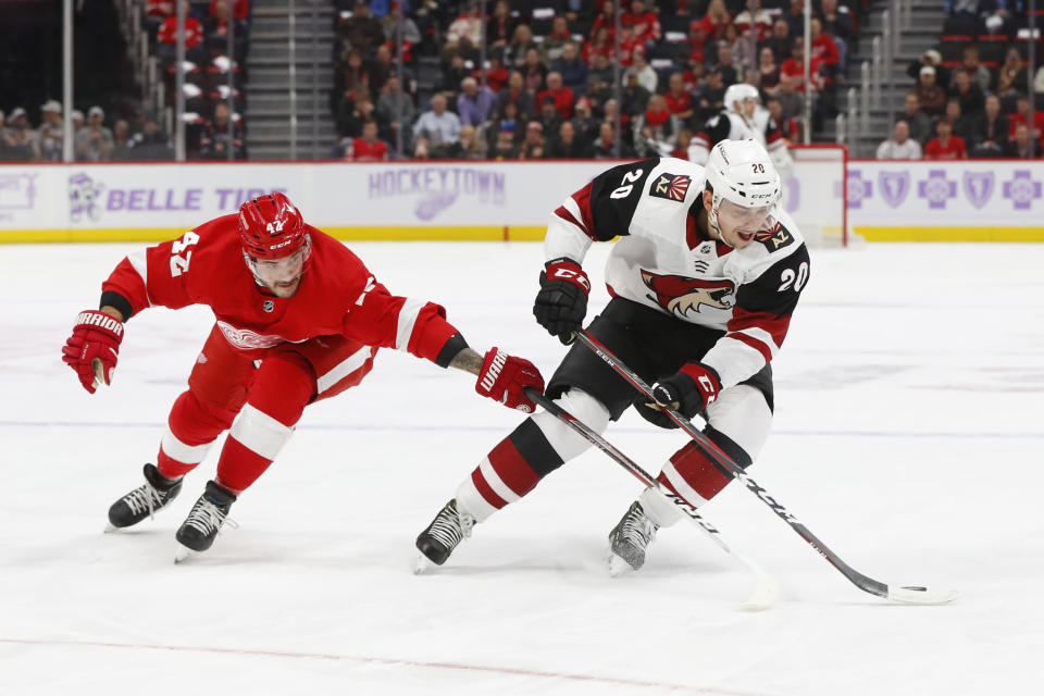 Arizona Coyotes center Dylan Strome (20) protects the puck from Detroit Red Wings right wing Martin Frk (42) in the first period of an NHL hockey game Tuesday, Nov. 13, 2018, in Detroit. (AP Photo/Paul Sancya)