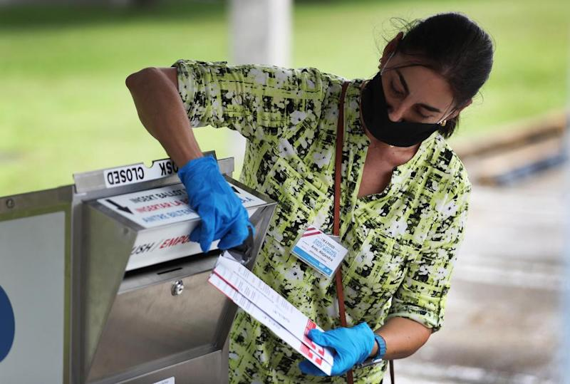 A poll worker places mail-in ballots in a drop box in Doral, Florida.