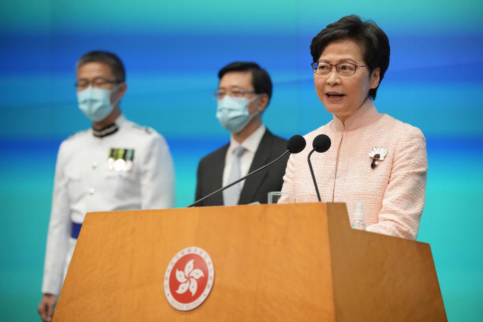 Hong Kong's Chief Executive Carrie Lam, right, speaks besides Chief Secretary John Lee, center, and Commissioner of Police Raymond Siu during a news conference in Hong Kong, Friday, June 25, 2021. China on Friday promoted Hong Kong's top security official to the territory's No. 2 spot as Beijing continues to clamp down on free speech and political opposition. (AP Photo/Kin Cheung)