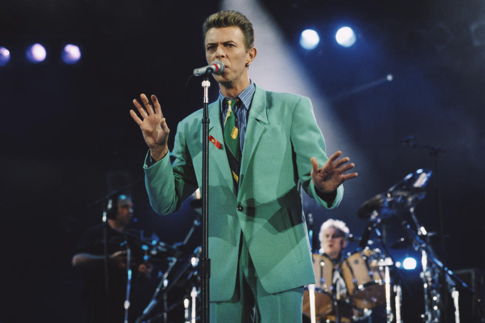 David Bowie (1947 - 2016) performs on stage at the Freddie Mercury Tribute Concert for AIDS Awareness, Wembley Stadium, London, 20th April 1992. Queen drummer Roger Taylor performs behind. (Photo by Michael Putland/Getty Images)