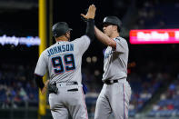 Miami Marlins' Trevor Rogers, right, and first base coach Keith Johnson celebrate after Rogers' single off Philadelphia Phillies pitcher Brandon Kintzler during the seventh inning of a baseball game, Wednesday, May 19, 2021, in Philadelphia. (AP Photo/Matt Slocum)