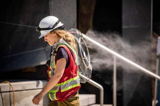 A construction worker uses a misting fan to cool down at a work site in Vancouver on June 28.  (Ben Nelms/CBC - image credit)