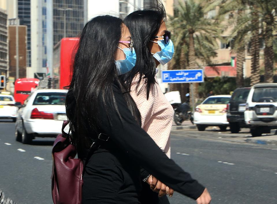 People wear protective masks in Kuwait City on February 27, 2020 amidst a world epidemic of cononavirus COVID-19. - The new coronavirus hit four more Middle Eastern states, with Bahrain, Iraq, Kuwait and Oman reporting new cases and the UAE calling on its citizens not to travel to Iran and Thailand. Kuwait, for its part, called off celebrations for the Gulf state's national day, as it confirmed its first three cases of the virus, all connected to Iran. (Photo by YASSER AL-ZAYYAT / AFP) (Photo by YASSER AL-ZAYYAT/AFP via Getty Images)